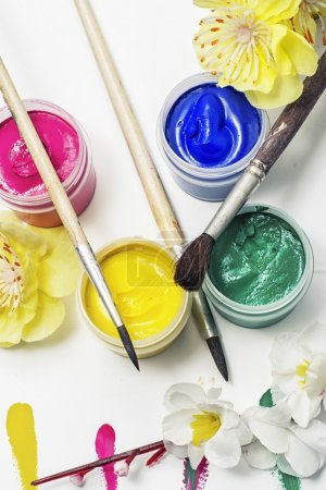 Photo for Paint for painting in cans and composition with flowers in the spring - Royalty Free Image