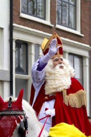 Saint Nicolaas on his white horse riding through the streets of