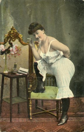 Vintage postcard, depicts a woman in pantaloons and a cigarette, circa 1908