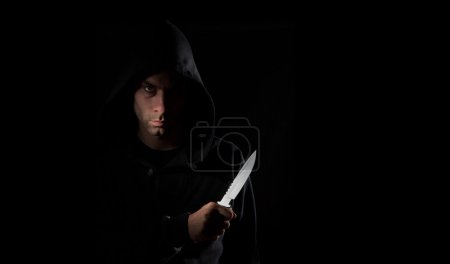 Photo for A dangerous hooded man standing in the dark and holding a shiny knife - Royalty Free Image