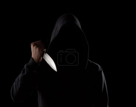 Photo for A dangerous hooded man standing in the dark and holding a shiny knife. Face can not be seen - Royalty Free Image