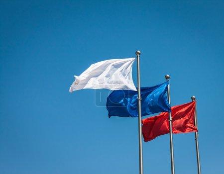 Photo pour Drapeaux blancs, bleus et rouges contre le ciel bleu. - image libre de droit