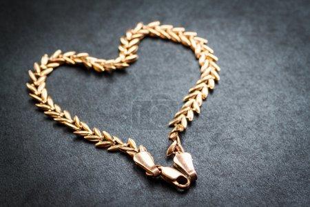 Photo pour Chaîne en or en forme de coeur sur fond sombre. Prise de vue macro avec faible profondeur de champ. Concentration sélective . - image libre de droit
