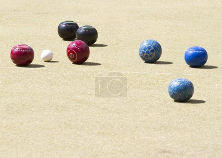 Photo for Bowls or lawn bowls is a sport which played on outdoor lawn which is natural grass or artificial turf. The objective of the game is to roll balls which is to stop close to a small ball jack or kitty. - Royalty Free Image
