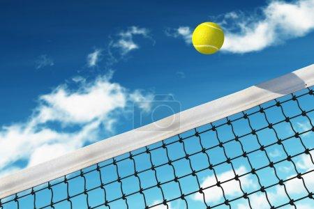 Photo pour Balle de tennis sur filet avec fond ciel - image libre de droit