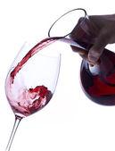 Nalévá červené víno z karafy izolované na bílém