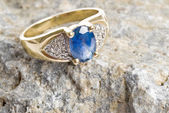 Gold Ring with Sapphire and Diamonds Sitting on a Piece of Rock