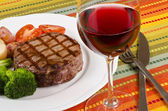 Barbecued Rib Eye Steak Served with Vegetables and a Glass of Red Wine