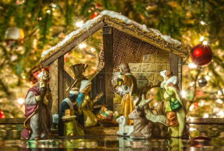 Photo for Old handmade nativity scene in front of a christmas tree - Royalty Free Image