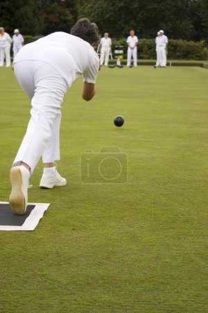 Photo for Woman bowling on lawn bowls green - Royalty Free Image