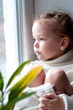 little girl looking from window