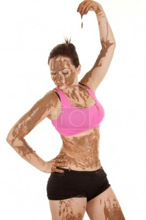 A woman covered in mud with it dripping from her f...