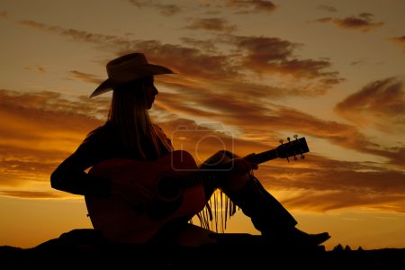 Photo for A cowgirl sitting on the ground playing her guitar with a beautiful sunset in the background. - Royalty Free Image