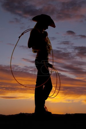 Photo for A silhouette of a woman looking down at the ground holdin on to her rope - Royalty Free Image