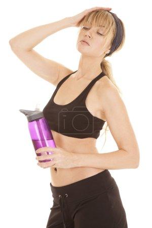 Photo pour Une femme avec sa main sur le dessus de sa tête tenant sa bouteille d'eau . - image libre de droit