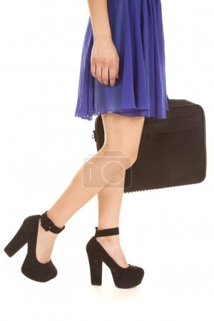 Photo for A woman walking in her blue dress holding on to a briefcase. - Royalty Free Image