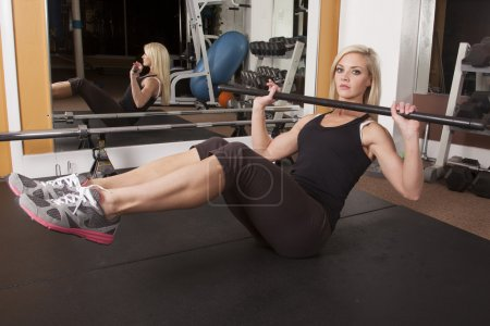 Woman gym sit up with bar