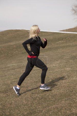 Photo pour Une femme qui court jusqu'à une colline où il y a toujours des neiges. - image libre de droit