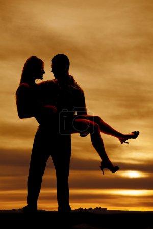 Photo pour Une silhouette d'un homme brandissant sa femme dans ses bras - image libre de droit