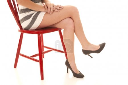 Photo for Woman sitting crossed legs in red chair with a striped skirt. - Royalty Free Image
