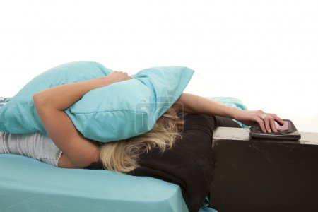 A woman laying on her pillow with a pillow over he...