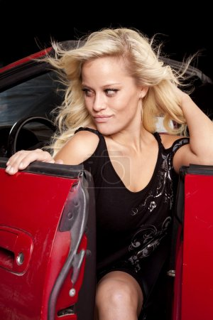 A woman is getting out of her convertible car in a sexy black dress.