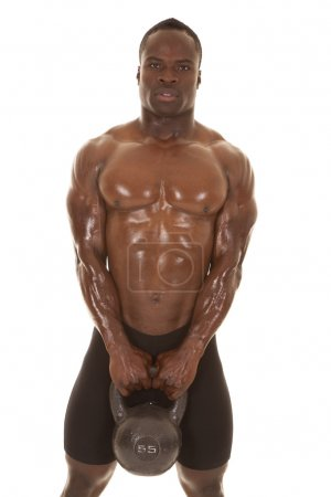 Photo for An African American man shirtless holding a weight. - Royalty Free Image