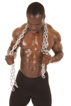 Photo for An African American man shirtless holding a chain. - Royalty Free Image
