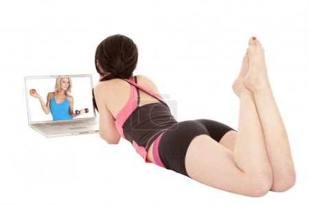Woman laying by computer looking at screen