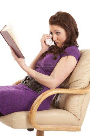 Photo pour Une femme lit un livre et tient un mouchoir sur son visage . - image libre de droit