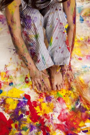 Photo for A woman sitting in wet paint showing off her hands and feet. - Royalty Free Image