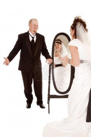 Groom waiting on his bride to finish looking in the mirror.