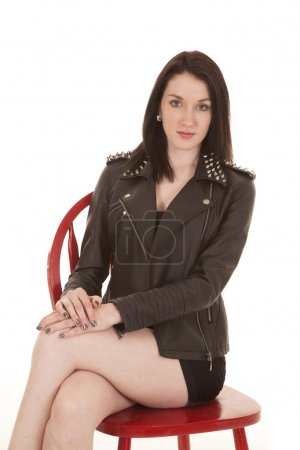 Photo for A woman sitting with legs crossed wearing a leather jacket. - Royalty Free Image