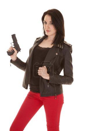 woman red pants black jacket gun looking