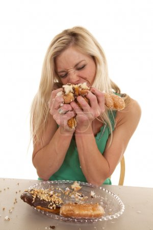Woman stuffing doughnuts onto mouth