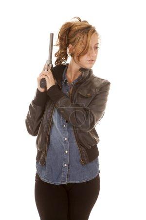 woman denim shirt black jacket gun look side