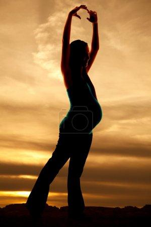 Photo pour Une femme danse enceinte silhouette au coucher du soleil. - image libre de droit