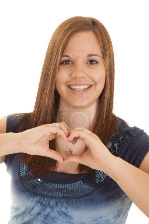 Photo pour Une femme tenant ses mains en forme de cœur avec un sourire sur son visage . - image libre de droit