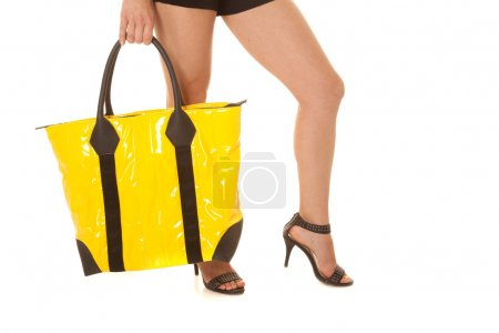 Woman legs yellow bag hold side