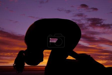Silhouette woman knees head down