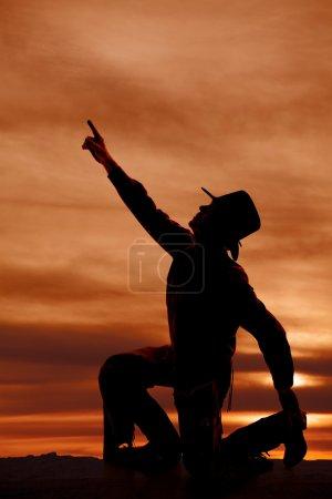 Photo pour Une silhouette d'un cow-boy pour atteindre son bras jusqu'au ciel - image libre de droit