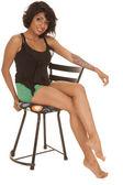 Hispánský žena sedět nohy židlí červené rty, úsměv