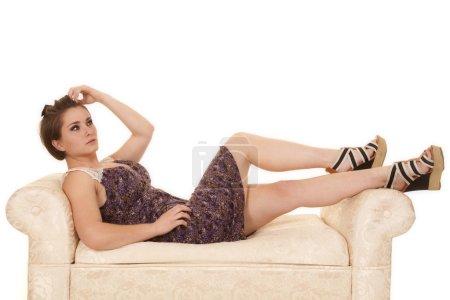 woman purple dress lace shoulders lay bench