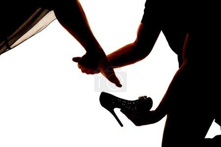 Photo pour Une silhouette d'un homme placé sur une chaussure de femme . - image libre de droit
