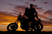 couple on motorcycle her lean back him hold