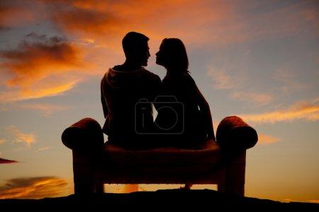 Photo pour Une silhouette de couple assis sur un banc en plein air . - image libre de droit