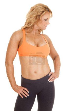 Mature woman orange bra stand look side