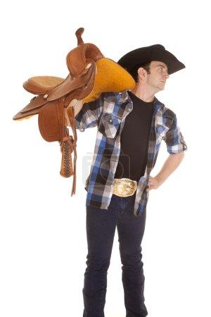 Cowboy holding saddle on shoulder