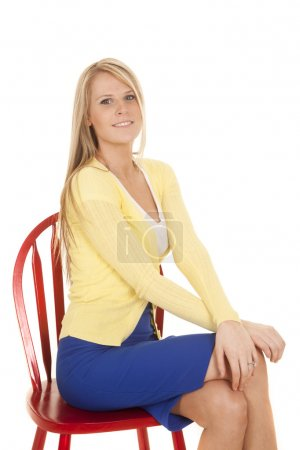Photo for A woman sitting on a red chair in her yellow and blue business outfit. - Royalty Free Image