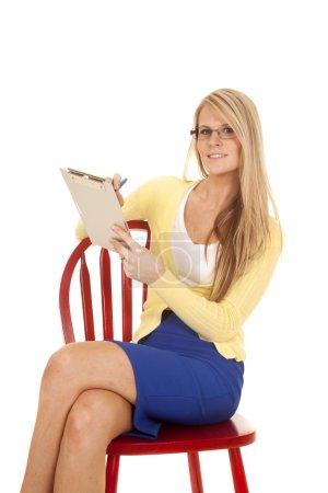 Photo pour Une femme assise sur sa chaise prend des notes sur son clip board . - image libre de droit